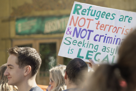 BRISBANE, AUSTRALIA - JUNE 20: Rally goer holding anti- immigration policy at World Refugee Day Rally June 20, 2015 in Brisbane, Australia