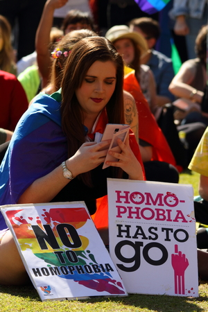 abbott: BRISBANE, AUSTRALIA - AUGUST 8 2015: Unidentified rally goer with anti homophobia sign at Marriage Equality Rally August 8, 2015 in Brisbane, Australia