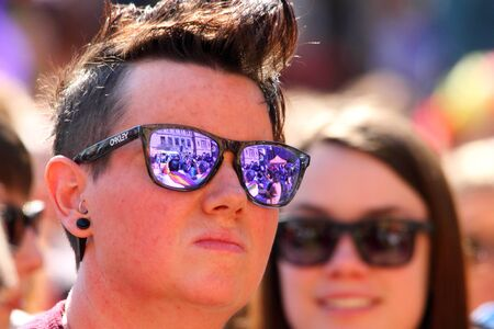 abbott: BRISBANE, AUSTRALIA - AUGUST 8 2015:Unidentified rally goer with gay flags reflected in glasses at  Marriage Equality Rally August 8, 2015 in Brisbane, Australia