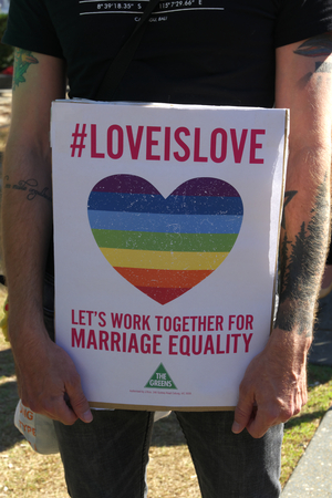 wedding parade: BRISBANE, AUSTRALIA - AUGUST 8 2015:#loveislove sign being held at  Marriage Equality Rally August 8, 2015 in Brisbane, Australia