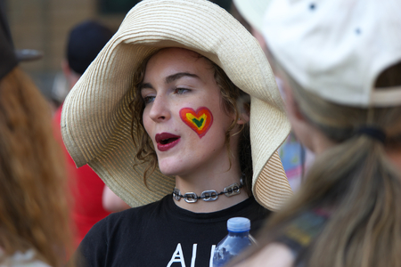 abbott: BRISBANE, AUSTRALIA - AUGUST 8 2015:Unidentified rally goer with rainbow heart at Marriage Equality Rally August 8, 2015 in Brisbane, Australia