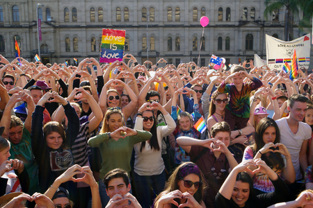 senate elections: BRISBANE, AUSTRALIA - AUGUST 8 2015: Crowds making love heart hand sign at Marriage Equality Rally August 8, 2015 in Brisbane, Australia