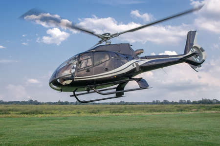 Beautiful view of a helicopter taking off from a grassy airport. Horizontal photo. Stock Photo