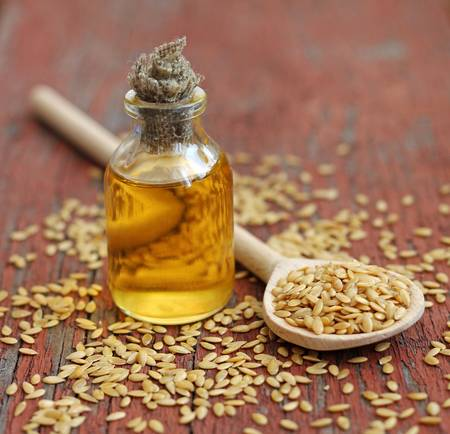 linseed oil in bottle on wooden background, close-up
