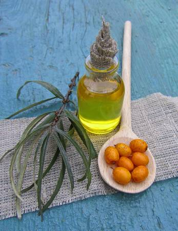 sea buckthorn oil in jar on blue wooden background, close-up Stock Photo