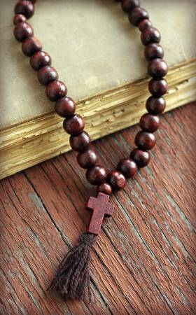 rosary beads and holy bible on wooden background, close-up photo