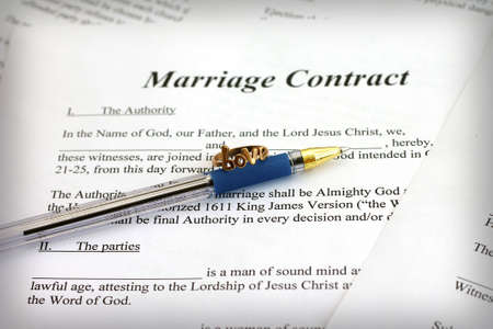 Marriage contract with pen and ring, close-up photo