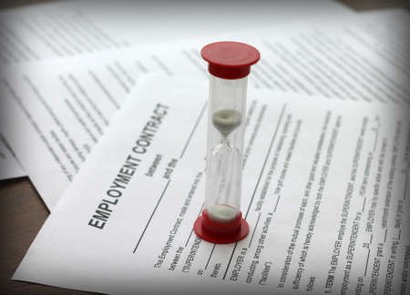 employment contract and hourglass, close-up