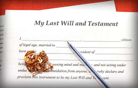 Last Will and Testament form with gold jewelry on red background, close-up photo