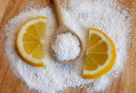 citric acid in wooden spoon with lemon, close-up