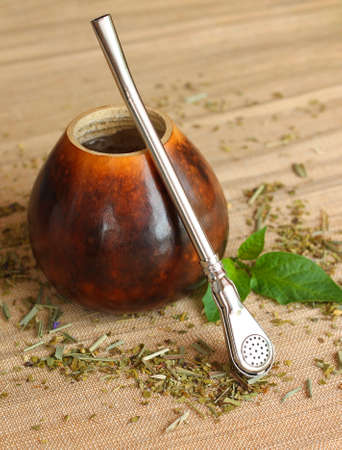 mate infusion: Calabash with yerba mate tea on canvas background, close-up