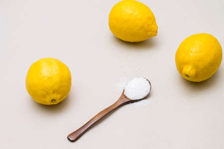 citric acid: Citric acid in wooden spoon and fresh lemons, on gray background Stock Photo