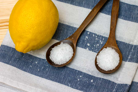 citric acid: Wooden spoon with citric acid on striped tablecloth, close-up
