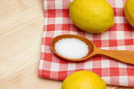 citric acid: Close-up of citric acid in wooden spoon on red tablecloth