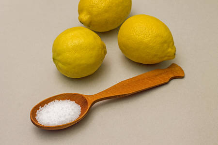 citric acid: Citric acid in spoon on background of lemons. Close-up
