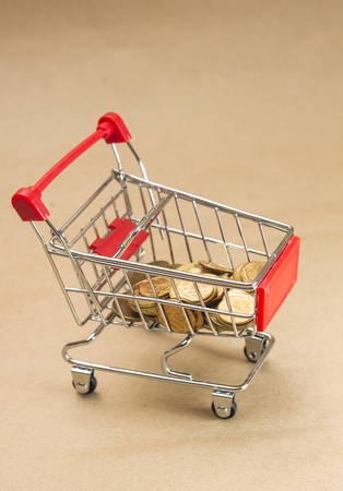 pushcart: Pushcart with coins. Concept of shopping, on brown background Stock Photo