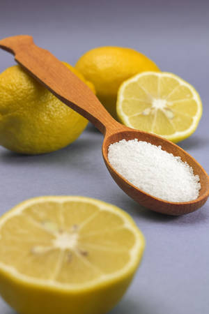 citric acid: Citric acid in wooden spoon and lemons, on blue background