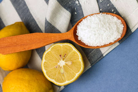 citric acid: Image of lemons and citric acid in wooden spoon, close-up