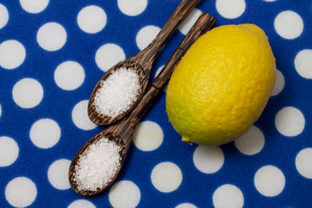 Citric acid in variegated wooden spoons, on blue polka dot background 写真素材