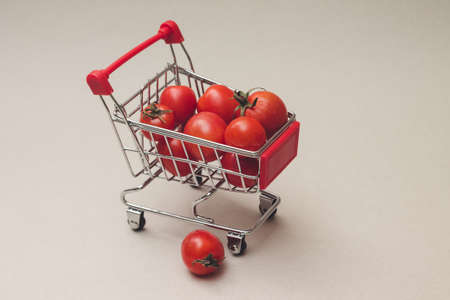 Photo of small tomatoes in a food trolley, on gray background