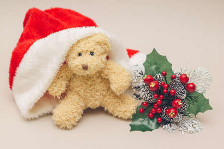 Image of Teddy bear in christmas cap, on grey backdrop Reklamní fotografie