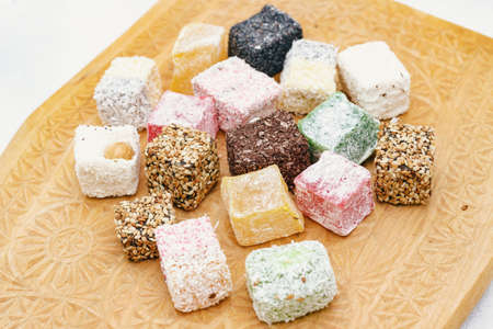 Assorted Turkish delight on a carved wooden board, close-up Reklamní fotografie