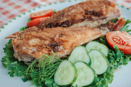Food photo. Appetizing fried fish with vegetable, close-up