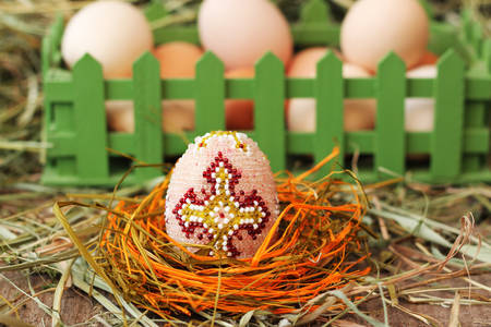Easter holiday concept. Photo in studio. Beaded egg with hay