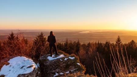 Young Man op zoek naar de zonsondergang op een koude januari avond Stockfoto