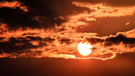 Dramatic Sunset behind clouds photo