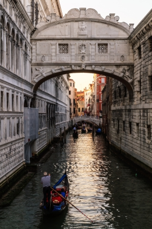 Ponte dei Sospiri  Picture of the famous romantic closed bridge Ponte dei Sospiri to the historical prison at the lagoon city of stone Venice in the sunset with gondola photo