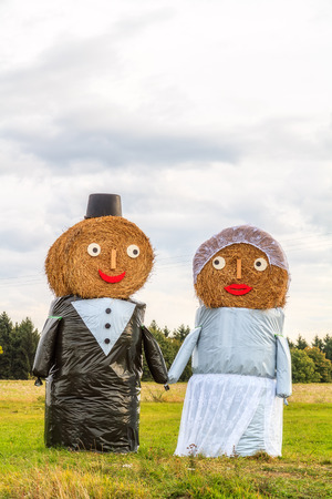 Marriage Tradition in Bavaria  Lovely Bridal Couple Puppets made out of Hay Bale with Suit and Wedding Dress in Europe in Autumn Stock Photo - 22737407