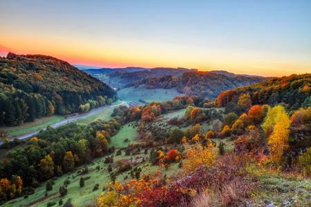 Idilliaco paesaggio di autunno con Colorful arancio dorato alberi vicino a un incantevole Country Road nelle rocciose Giura di Baviera, Germania Tramonto in autunno con un meraviglioso cielo sereno nella campagna rurale photo