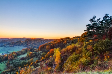 Idyllic Autumn Scenery with Colorful Orange Golden Trees near a lovely Country Road in the rocky Jura Mountains of Bavaria, Germany  Sunset in Fall with a wonderful clear sky in the rural countryside  photo