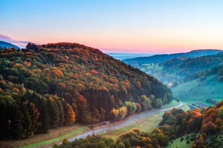 Idyllic Autumn Scenery with Colorful Orange Golden Trees near a lovely Country Road in the rocky Jura Mountains of Bavaria, Germany  Sunset in Fall with a wonderful clear sky in the rural countryside