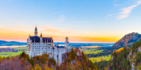 munich: Neuschwanstein, Lovely Autumn Landscape Panorama Picture of the fairy tale castle near Munich in Bavaria, Germany with colorful trees in the morning hours Editorial
