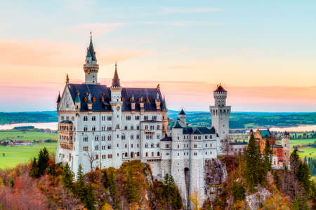 Neuschwanstein, Lovely Autumn Landscape Panorama. Picture of the fairy tale castle near Munich in Bavaria, Germany with colorful trees in the morning hours