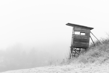 Hunting Place in January  Wooden stand  Hoar Frost on the Ground  Black and White  Low Stratus in the Morning  Atmosphere of Melancholy photo