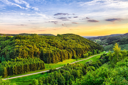 Fantastic Franconian Spring Landscape in Germany. Beautiful Road in the forrest hills of northern Bavaria at sunset. Fresh Deciduous Forest Scenery Standard-Bild