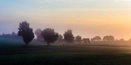 European Foggy Morning Sunrise in Franconia. Fog on the Ground. Late September Colors and Trees. Picuresque and Moody Atmosphere in Germany photo