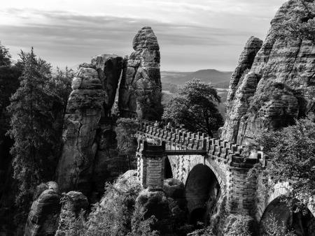 german swiss: Landmark Bastion Bridge, german Basteibruecke, in the saxonian swiss in Saxony near Dresden, Germany. Vintage Black and White Picture