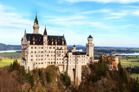 neuschwanstein: Neuschwanstein, Lovely Autumn Landscape Panorama Picture of the fairy tale castle near Munich in Bavaria, Germany with colorful trees in the morning hours Editorial