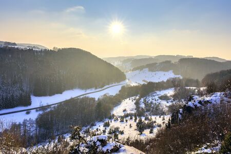 trecking: Cold snowy winter sunset in Bavaria, Germany. Sweet Solitude. White and Lonely hill Landscape. Lovely orange sunset