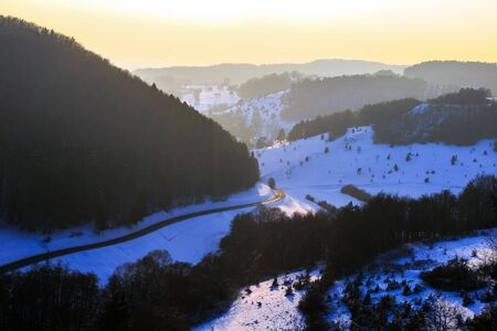 Cold snowy winter sunset in Bavaria, Germany. Sweet Solitude. White and Lonely hill Landscape. Lovely orange sunset