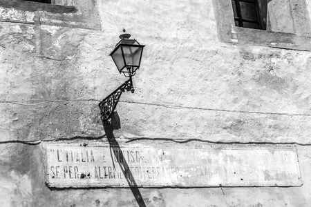 fading: Lantern in Sicily, Italy with illegible fading sign on midday. Vintage Black and White. Strong Shadows