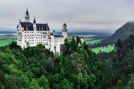 munich: Famous Architecture and Landmark near Munich, Germany. Castle Neuschwanstein at Fuessen in Late Summer on a cold and wet day. Amazing Hill Landscape Stock Photo