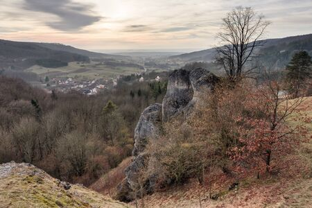 jura: Early Spring Landscape Scene. Old jurassic Coastal Rocks from the prehistoric ocean in Bavaria, Germany, today part of the franconian swiss. Barren Landscape and Lovely Sunset