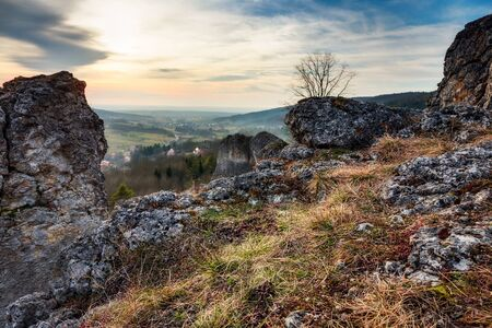 jurassic: Early Spring Landscape Scene. Old jurassic Coastal Rocks from the prehistoric ocean in Bavaria, Germany, today part of the franconian swiss. Barren Landscape and Lovely Sunset