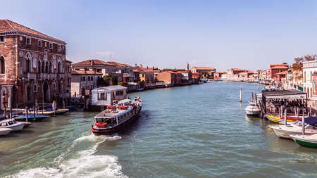 Murano: MURANO, ITALY - SEPTEMBER 06 2013: Scene from the Canals of Murano. Boats on the water. Old Architecture. Sunny Blue Sky