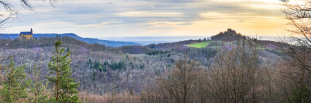 Sunset in the Hills of Franconia, Germany on evening to early April. Barren trees in the forrest. Panoramic format. Rural Countryside. Mountain Chapel and Castle